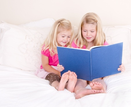 14416902 - sisters on bed reading book